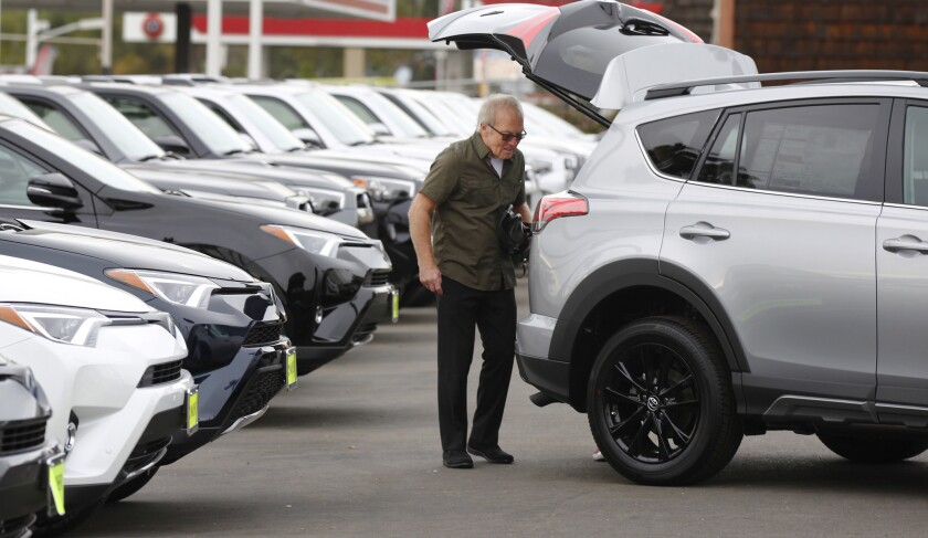 In a file photo from November 2017, a customer looks over a Toyota RAV4 at Mossy Toyota in Pacific Beach. After roaring back from the depths of the Great Recession, the new car market is slowing down.