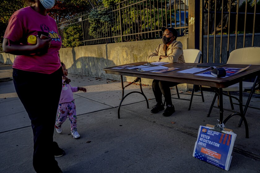 A woman and child pass Laurae Caruth at a table where she registers voters in New York.
