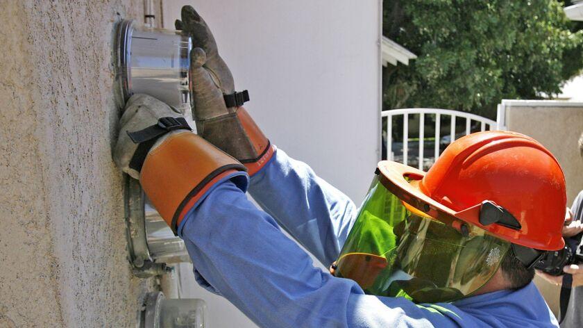 Utility Partners of America field tech Robert Jordan installs smart electric meters at an apartment