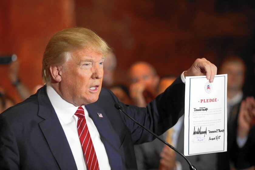 Donald Trump holds up a pledge -- dated Aug. 3. He later tweeted a document with the correct date.