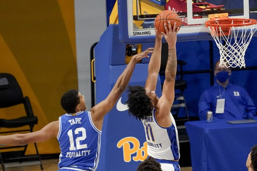 Pittsburgh's Justin Champagnie (11) dunks after getting by Duke's Patrick Tape (12) during the first half of an NCAA college basketball game, Tuesday, Jan. 19, 2021, in Pittsburgh. (AP Photo/Keith Srakocic)