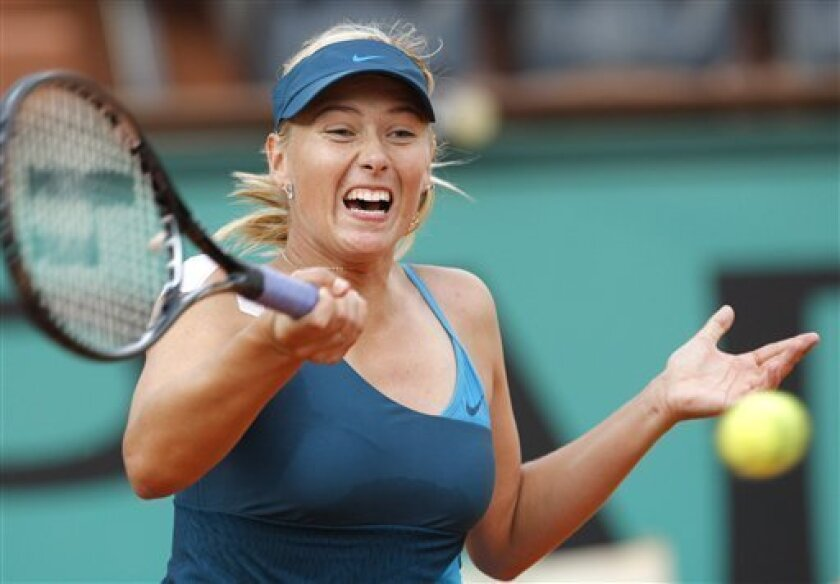 Russia's Maria Sharapova returns the ball to China's Li Na during their fourth round match of the French Open tennis tournament at the Roland Garros stadium in Paris, Sunday May 31, 2009. (AP Photo/Christophe Ena)