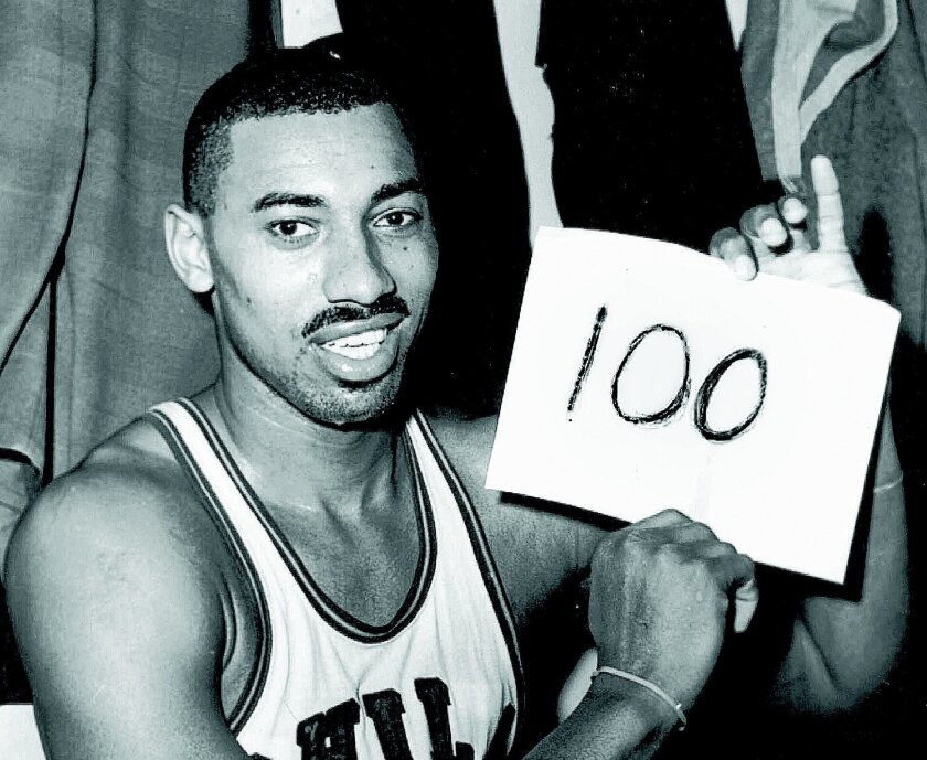 """In this March 2, 1962 file photo, Wilt Chamberlain of the Philadelphia Warriors holds a sign reading """"100"""" in the dressing room in Hershey, Pa., after he scored 100 points, as the Warriors defeated the New York Knickerbockers 169-147. For 50 years, Chamberlain's 100-point night has stood as one of sports magic numbers."""