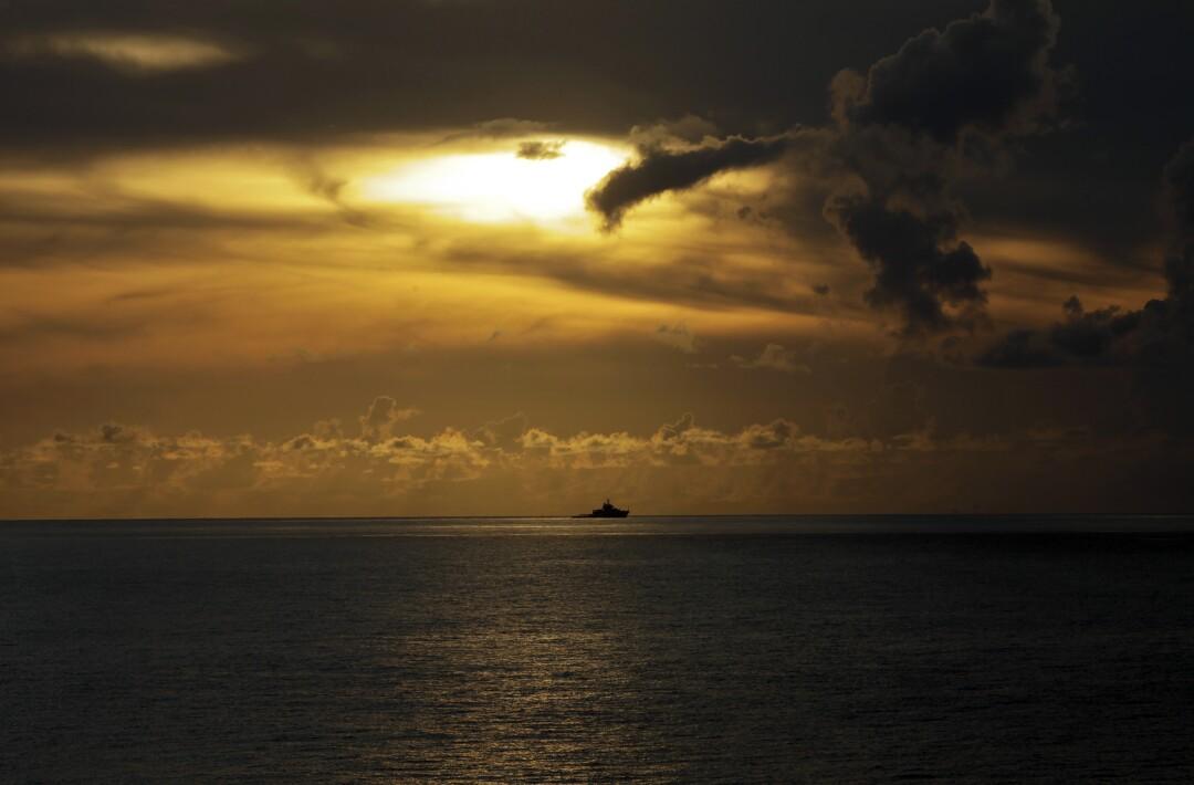 Ein weit entferntes Schiff am Horizont unter einem sich verdunkelnden gelb-orangefarbenen Himmel