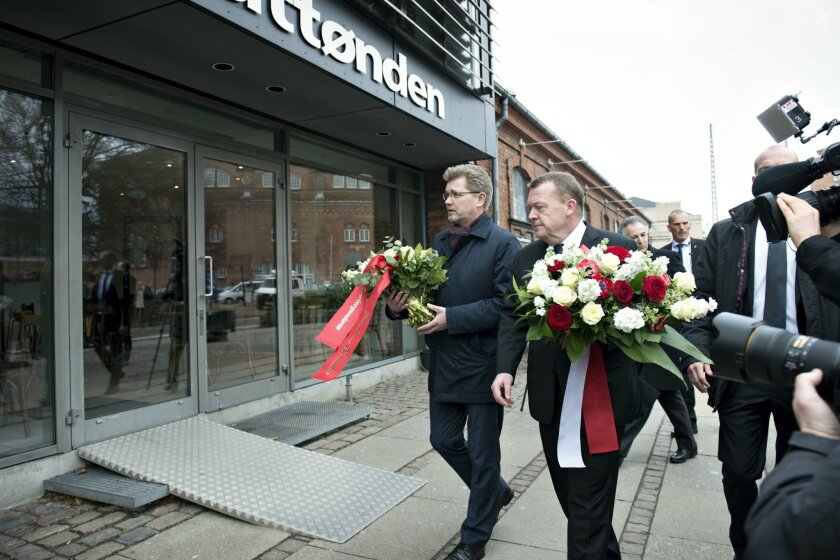 Prime Minister Lars Lokke Rasmussen and Mayor of Copenhagen Frank Jensen, left, places flowers in front of the memorial plates of Finn Norgaard, the victim of the shooting attacks a year ago at Krudttonden in Copenhagen, Denmark, Sunday, Feb. 14, 2016. A gunman opened fire Feb. 14, 2015 on a Copenh