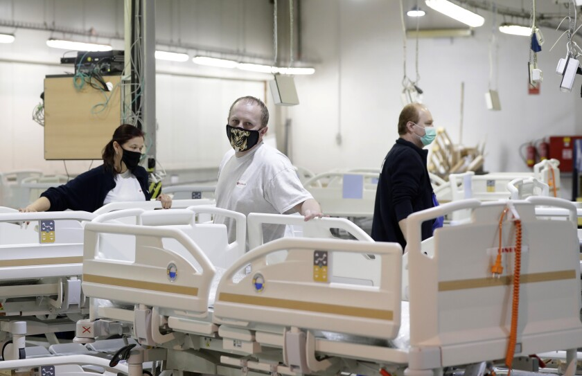 Workers add the final touches to a hospital bed being assembled at the Linet factory in Slany, Czech Republic, Monday, Oct. 19, 2020. A Czech hospital bed maker with a full order book received one more order that was impossible to turn down. The company was approached by Prime Minister Andrej Babis to deliver beds for a military field hospital for 500 COVID-19 patients, to be built this week in Prague. (AP Photo/Petr David Josek)