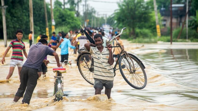 Nepalis navigate floodwaters in Birgunj, Parsa district, south of Katmandu on Aug. 13, 2017.