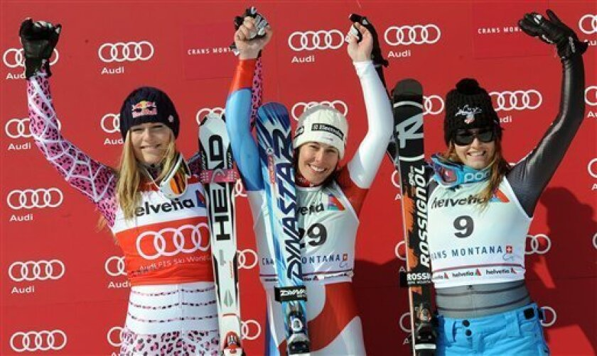Dominique Gisin of Switzerland, center, winner of an alpine ski, Women's World Cup super-G, celebrates on the podium with second placed Lindsey Vonn of the United States, left, and third placed Julia Mancuso of the United States, in Crans Montana, Switzerland, Sunday, March 7, 2010. (AP Photo/Armando Trovati)