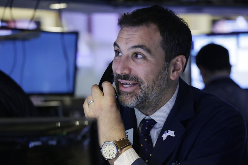 A trader follows prices before the opening bell at the New York Stock Exchange on Friday.