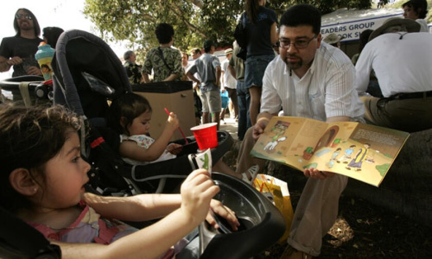 """Gerardo Campos, right, reads, """"Picadillo the Armadillo,"""" book to his daughter Angelina, 3, left, and niece Omega Flores, 1, during the Los Angeles Times Festival of Books in 2008."""