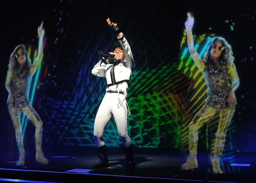 Janelle Monae, center, performs alongside 'holograms' of M.I.A. during a launch party for the Audi M3 on April 3, 2014.
