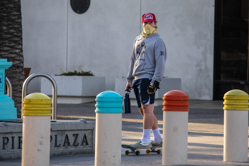 A man wearing a face covering skates along Pier Plaza, in Hermosa Beach, in April.