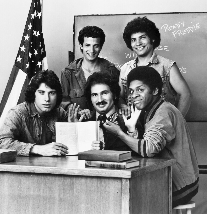 """Cast of """"Welcome Back Kotter."""" From left seated: John Travolta as Vinnie Barbarino, Gabe Kaplan as Gabe Kotter, and Lawrence Jacobs as """"Boom Boom"""" Washington. In back are Ron Palillo as Horshack, left, and Robert Hegyes as Juan Luis Padro Epstein."""