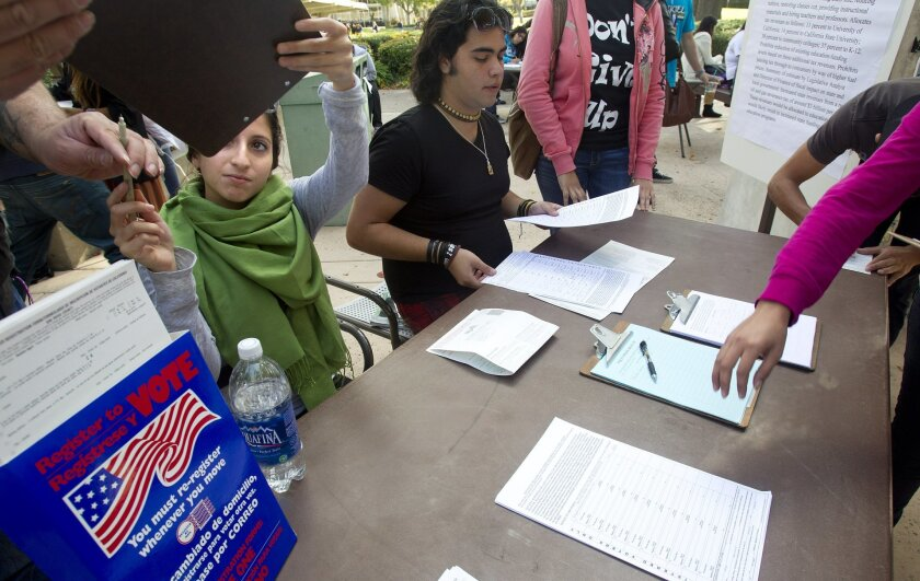 Iliana Cervantes, left, hands a petition to a fellow Southwestern College student as she and Diego De Aczua  help register students to vote and sign a petition supporting a tax on oil to support education in California.
