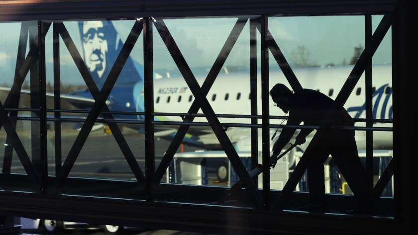 FILE- In this March 4, 2019, file photo a worker cleans a jet bridge before passengers boarded an Al
