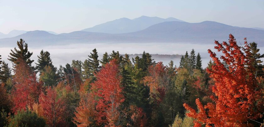 FILE - In this Sept. 28, 2014, file photo, fog sits in the valley of the White Mountains as leaves change colors from Milan Hill in Milan, N.H. (AP Photo/Jim Cole, File)