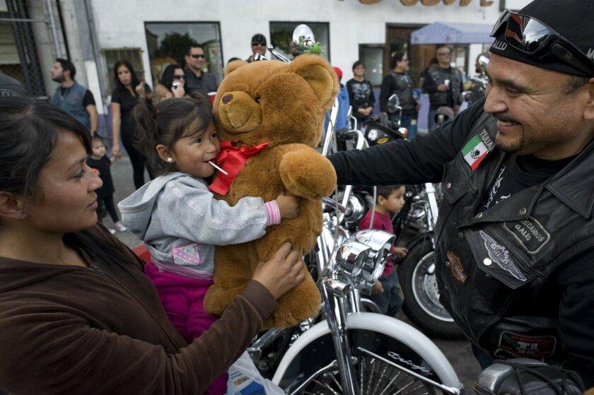 Rene Castro, right, gives a teddy bear to Jasmine Torres during Sunday's Tijuana Toy Run.