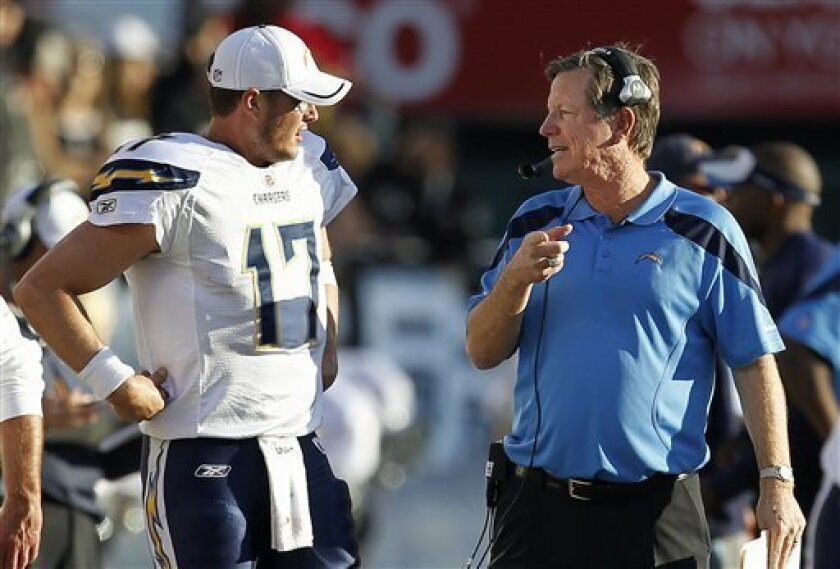 San Diego Chargers quarterback Philip Rivers (17) talks with head coach Norv Turner during the third quarter of an NFL football game against the Oakland Raiders in Oakland, Calif., Sunday, Jan. 1, 2012. (AP Photo/Tony Avelar)