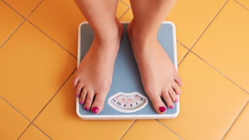 A pair of female feet standing on a bathroom scale.