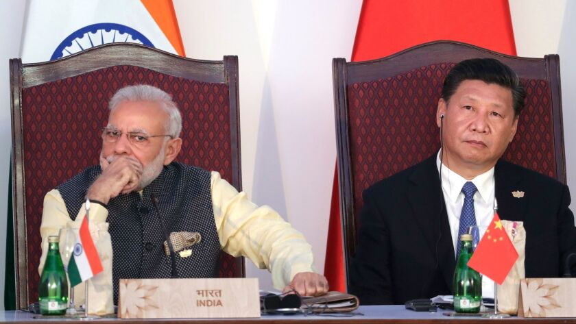 Indian Prime Minister Narendra Modi, left, and Chinese President Xi Jinping listen to a speech durin