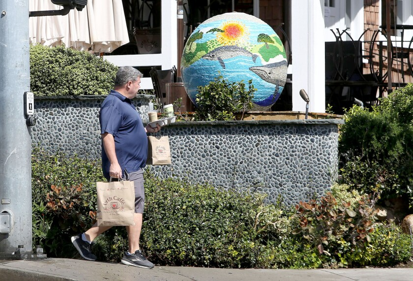 A patron of Urth Caffe in Laguna Beach carries a takeout order as local restaurants and other essential businesses comply with orders to prevent gatherings during the coronavirus pandemic.