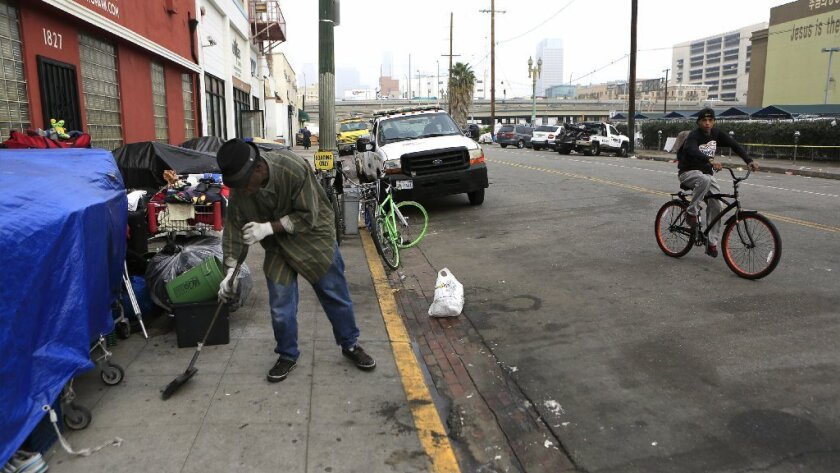 Dozens of California cities have laws targeting the homeless. Above, a skid row resident sweeps the sidewalk where his belongings are gathered.
