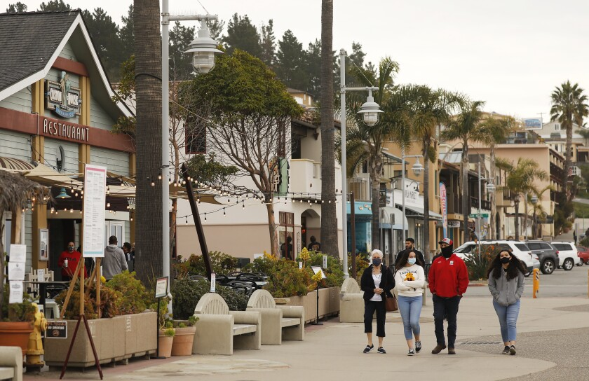 A family walks down the street in Avila Beach in San Luis Obispo County