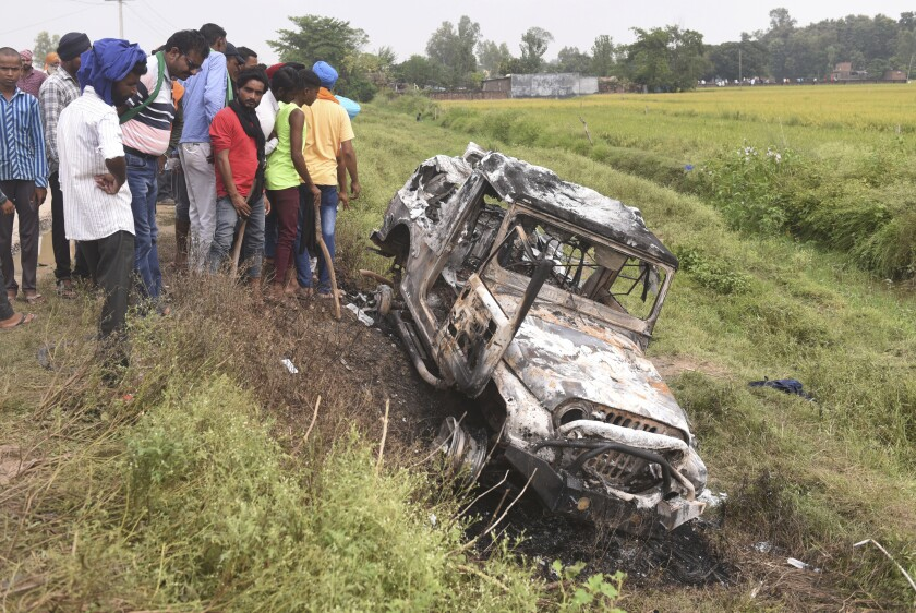 Villagers watch a burnt car which run over and killed farmers on Sunday, at Tikonia village in Lakhimpur Kheri, Uttar Pradesh state, India, Monday, Oct. 4, 2021. Indian authorities suspended internet services and barred political leaders from entering the northern town Monday to calm tensions after nine people were killed in a deadly escalation of a yearlong demonstration against contentious agriculture laws. (AP Photo)
