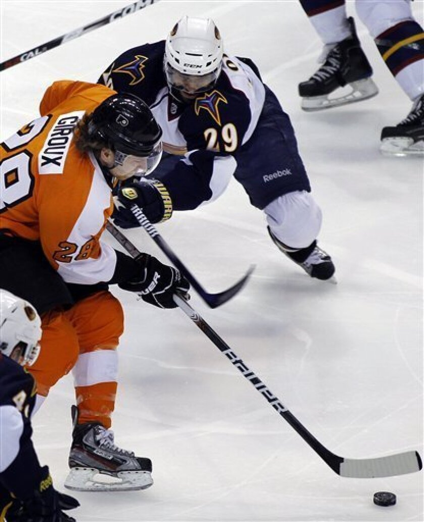 Philadelphia Flyers' Claude Giroux, left, battles for control of the puck with Atlanta Thrashers' Johnny Oduya in the first period of an NHL hockey game on Thursday, March 31, 2011, in Philadelphia. (AP Photo/Tom Mihalek)