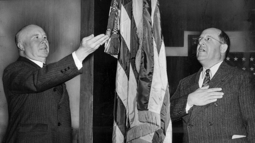 March 29, 1943: Vierling Kersey, Superintendent of Schools, left, and Roy J. Becker, Board of Education president, demonstrate old and new methods of saluting Old Glory.