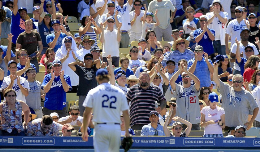 Dodger fans applaud Clayton Kershaw as he comes off the mound.