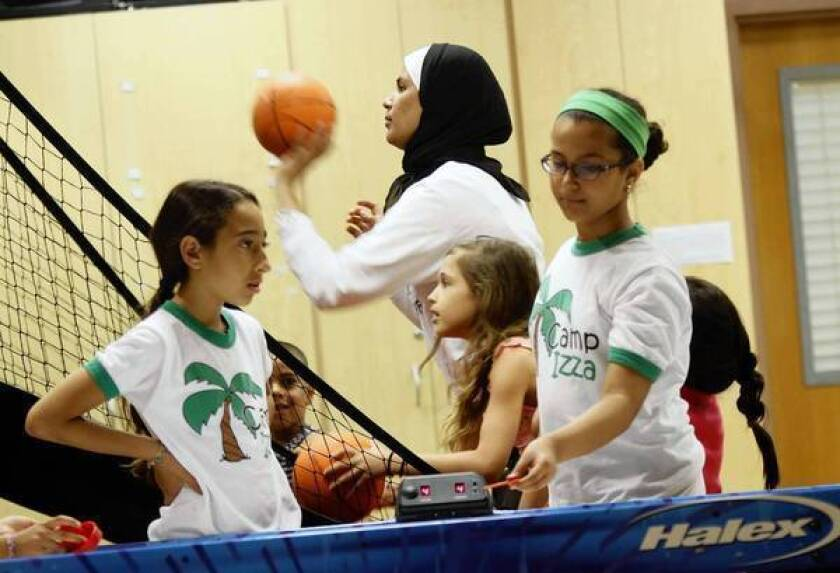 Campers and counselors play indoor sports at Camp Izza's Irvine location, the New Horizon school campus.