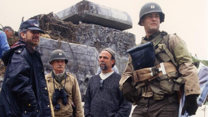 "Preparing for action on their version of Omaha Beach: director Steven Spielberg from left, senior military advisor Dale Dye, production designer Tom Sanders, and Tom Hanks on the set of ""Saving Private Ryan."""