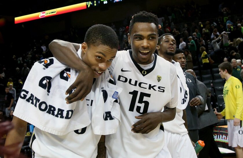 Oregon's Joseph Young, left, is congratulated by teammate Jalil Abdul-Bassit after the Duck's 95-72 win over Washington State in an NCAA college basketball game in Eugene, Ore., Sunday, Feb. 8, 2015. Young lead the team with 29 points. (AP Photo/Chris Pietsch)