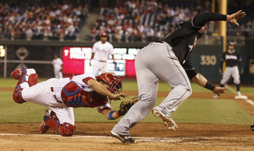 Philadelphia Phillies catcher Wil Nieves, left, tags out Miami Marlins' Justin Bour, right, who was trying to score on a hit by Reed Johnson during the seventh inning of a baseball game, Saturday, Sept. 13, 2014, in Philadelphia. (AP Photo/Chris Szagola)