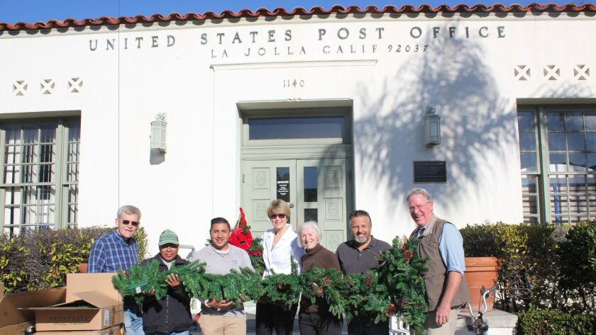 Volunteers Barry Bielinski, José Xinos, Israel Zea, Seonaid McArthur, Ann Craig, Raúl Albanez, John Peek hold the Christmas decorations for the La Jolla Post Office building.