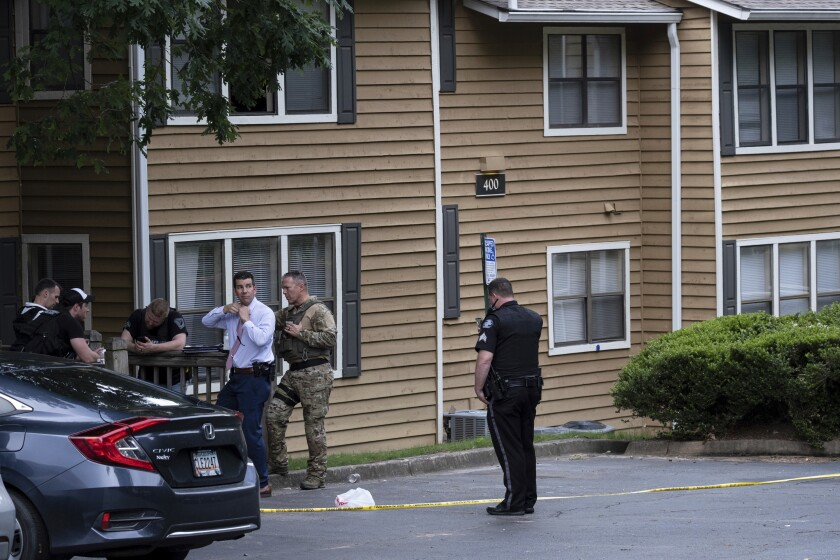 Law enforcement officers wait outside of a Sandy Springs, Ga., apartment where Gary Creek died Tuesday, June 8, 2021, following a SWAT standoff. Creek, a suspected Baltimore gang leader died from an apparent self-inflicted gunshot wound after a standoff with law enforcement Tuesday afternoon in an Atlanta suburb, authorities said. (AP Photo/Ben Gray)