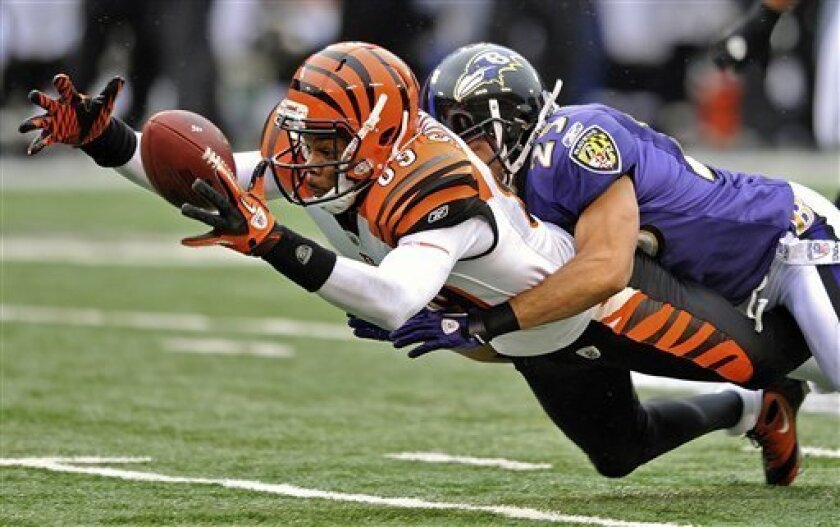 Cincinnati Bengals wide receiver Jerome Simpson fumbles the ball on a hit from Baltimore Ravens cornerback Chris Carr during the first half of an NFL football game in Baltimore, Sunday, Jan. 2, 2011. The Ravens recovered the fumble. (AP Photo/Gail Burton)