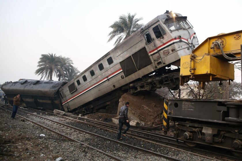 People gather at the site of a train derailment near Beni Suef, Egypt, Thursday, Feb. 11, 2016 that  injured dozens of people were injured as it was traveling north toward Cairo. Railroad accidents due to negligence are common in Egypt. Egyptians have long complained that the government has failed