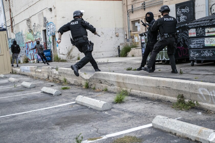 An LAPD officer chases a suspected looter in an alley behind Hollywood Boulevard.