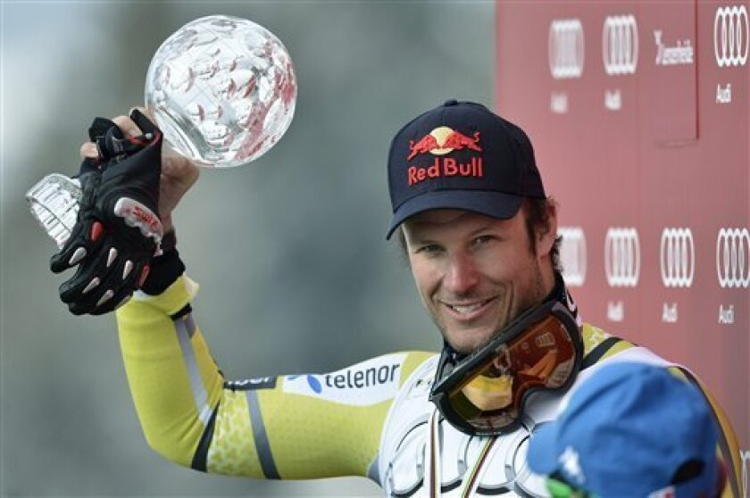 Aksel Lund Svindal of Norway lifts the crystal globe as the winner of the overall downhill men's World Cup after the men's World Cup Super G of the Alpine Ski World Cup finals, in Lenzerheide, Switzerland, Thursday, March 14, 2013. (AP Photo/Keystone, Laurent Gillieron)