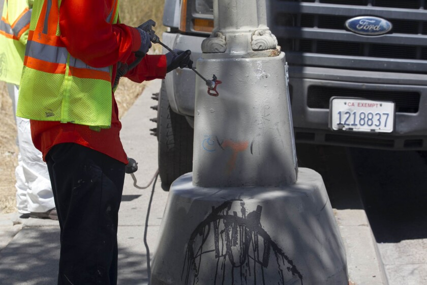 Graffiti on the base of a  light pole on the south side of University Avenue at 54th Street gets spray painted.