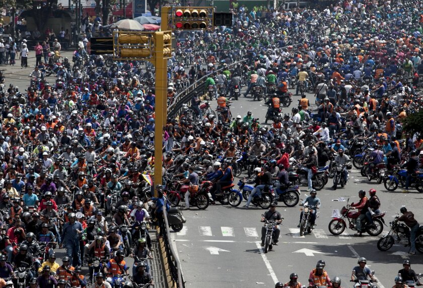 Motorcyclists protest a proposed nighttime curfew for two-wheelers in Caracas, Venezuela, Friday, Jan. 31, 2014. President Nicolas Maduro's government this month lent its support to proposals to ban motorcycles from circulating at night, arguing that the vehicles are used to carry out murders and k