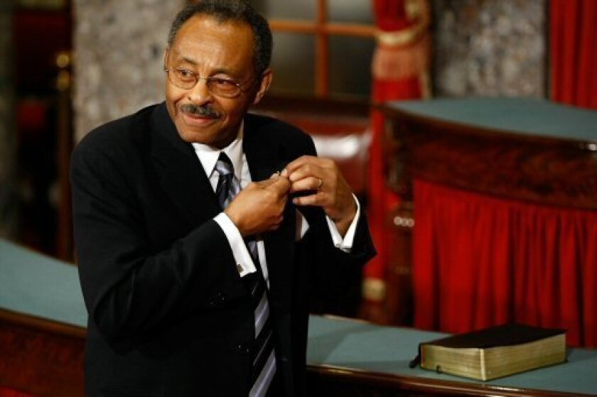 Senator Roland Burris (D-IL) puts on his Senate lapel pin before Vice President Dick Cheney swears him into the Senate at a ceremony in the Old Senate Chamber at the U.S. Capitol on January 15, 2009 in Washington, DC. (Photo by Chip Somodevilla/Getty Images)