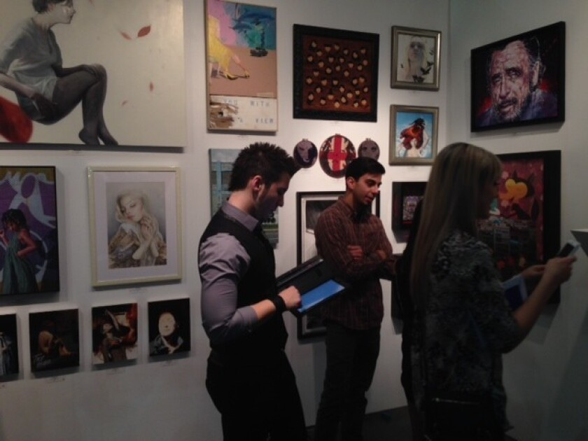 Young collectors peruse the Thinkspace Gallery booth at the LA Art Show.
