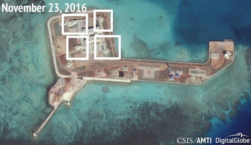 A satellite image from last month shows what CSIS Asia Maritime Transparency Initiative says appears to be anti-aircraft guns and weapons systems on the artificial island China built on Hughes Reef