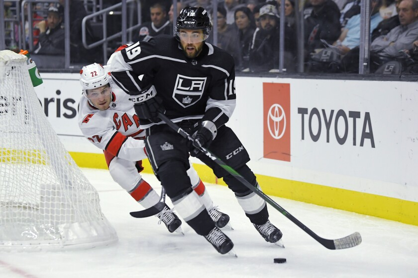 Kings left wing Alex Iafallo, right, moves the puck while under pressure from Carolina Hurricanes defenseman Brett Pesce during the second period on Tuesday at Staples Center.