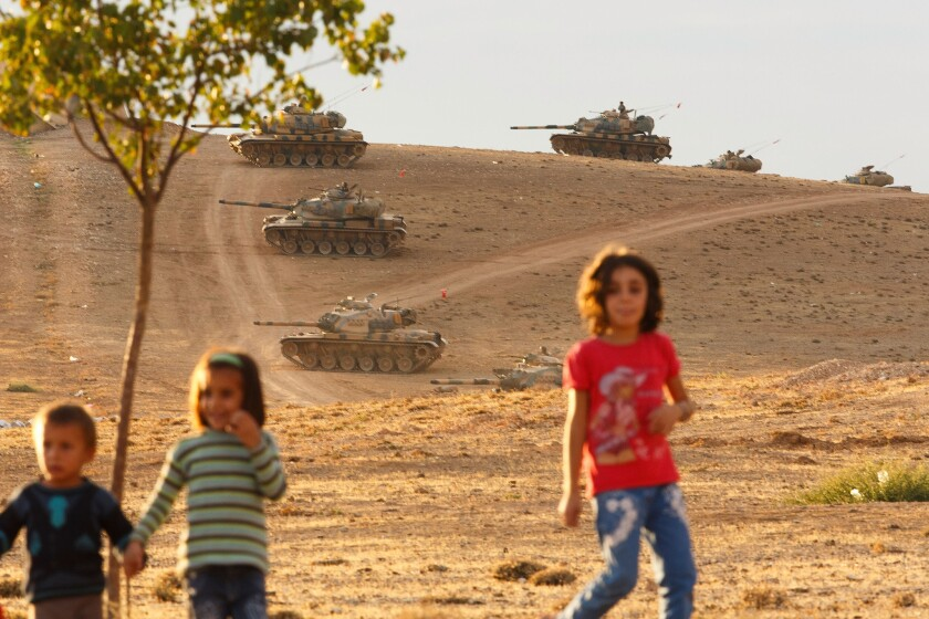 Children run in Sanliurfa, Turkey, while tanks from the Turkish armed forces are dispatched to the Turkish-Syrian border as clashes intensified with Islamic State militants on Monday.