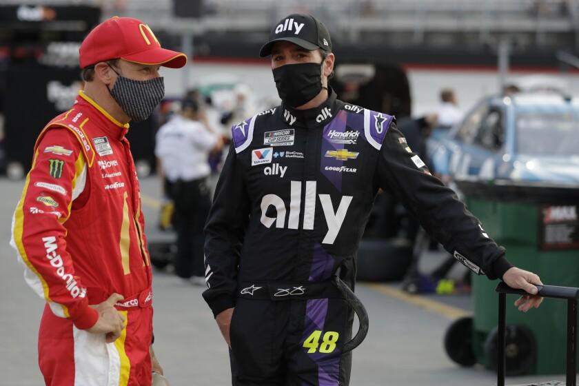 Matt Kenseth, left, and Jimmie Johnson (48) talk before a NASCAR All-Star auto race at Bristol Motor Speedway in Bristol, Tenn, Wednesday, July 15, 2020. (AP Photo/Mark Humphrey)