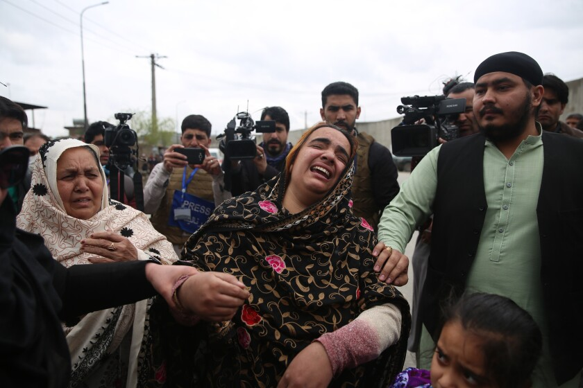Afghans mourn near the scene of an attack March 25 in Kabul.